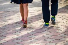 Marche dans des chaussures de sport le jour de trottoir au printemps Photographie stock libre de droits