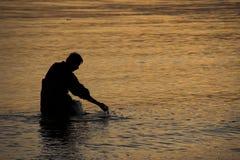 Marche dans l'eau du pêcheur au coucher du soleil   Photo stock