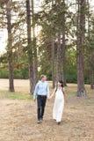 Marche de métis d'homme et de femme et tenir des mains dans la forêt ou le parc photos stock