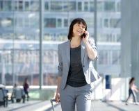 Marche et parler avec le téléphone portable à l'aéroport Image libre de droits