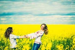 Marche extérieure de jolies filles dans le domaine dans des chemises de broderie Photographie stock libre de droits