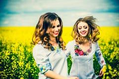 Marche extérieure de jolies filles dans le domaine dans des chemises de broderie Photo stock