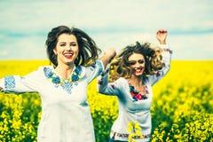 Marche extérieure de jolies filles dans le domaine dans des chemises de broderie Photos libres de droits