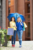 Marche intégrale de deux beaux amis féminins avec un parapluie et des paniers Image stock