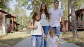 Marche masculine et femelle heureuse avec des enfants dehors banque de vidéos