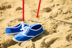 Marche nordique bâtons et chaussures violettes sur une plage sablonneuse Images stock