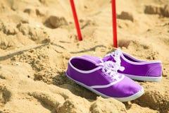 Marche nordique bâtons et chaussures violettes sur une plage sablonneuse Photos libres de droits