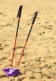 Marche nordique bâtons et chaussures violettes sur une plage sablonneuse Images libres de droits