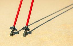 Marche nordique Bâtons rouges sur la plage sablonneuse Photos libres de droits