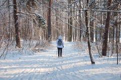 Marche nordique Femme dans une veste blanche avec un sac à dos augmentant dans paysage scénique de forêt froide un beau avec la n Images stock