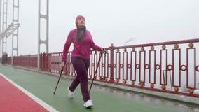 Marche nordique Jeune femme caucasienne potel?e trimardant avec les poteaux nordiques La partie ant?rieure suivent le tir clips vidéos