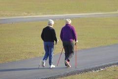 Marche nordique scandinave Deux femmes plus âgées sont engagées dans les sports même en bas du chemin pavé chronomètrent au print image libre de droits