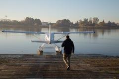 Marche pilote masculine vers l'eau d'hydravion photographie stock libre de droits