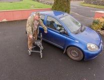 Marche supérieure d'homme masculin de vieillesse à la voiture avec la MOBILITÉ ROLLATOR LÉGER d'incapacité PLIANT ZIMMER de MARCH Photo stock