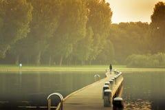 Marche sur un pont au lever de soleil d'or Image stock