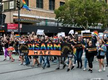 Marchers hold a `Disarm Hate`  banner at 2017 San Francisco Pride Parade. SAN FRANCISCO, CA – JUNE 25, 2017: Marchers hold a `Disarm Hate` gun control banner Royalty Free Stock Photo