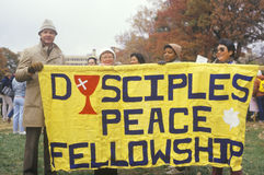 Marchers holding up banner promoting fellowship Royalty Free Stock Image