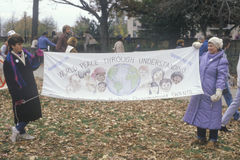 Marchers holding up a banner promoting world peace Royalty Free Stock Photography