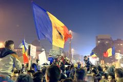 Marchers at #rezist protest, Bucharest, Romania. Marchers with flags and signs at #rezist protest in Bucharest, Romania at night Stock Images