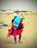 Marcheur abusif marchant sur la plage vendant des tissus de coton Images libres de droits