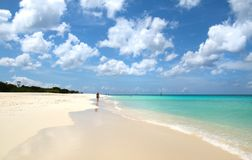 Marcheur blanc de plage de sable Eau de mer bleue et nuages dramatiques Oranjestad, Aruba Eagle Beach célèbre images stock