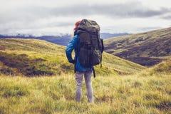 Marcheur de colline se tenant au milieu de la région sauvage de montagne Photographie stock libre de droits