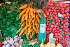 Marchewki, rzodkwie, cebule, czosnek przy Jarzynowym jarmarku kontuarem Zdjęcia Royalty Free