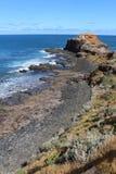 Marchez à la roche de pupitre le long des pierres noires de lave et du sol rouge différant de l'océan bleu et au ciel au cap Scha images stock
