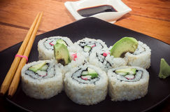 Marchez en crabe le petit pain de sushi avec l'avocat du plat noir Photo stock