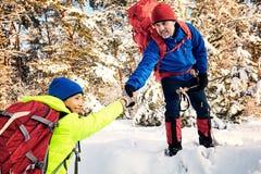 Marchez par la forêt d'hiver avec un sac à dos et une tente Photographie stock libre de droits