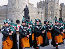 Marching band of the Royal Irish Rangers. The Royal Irish Rangers Pipe Band marching past a Statue of Queen Victoria at Windsor Castle, Uk, the Berkshire Home of Royalty Free Stock Image