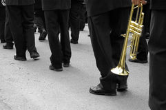 Marching Band Trumpeter. Black and white image of a marching band's legs with a lone trumpet singled out with colour.  Path embedded around trumpet Royalty Free Stock Images
