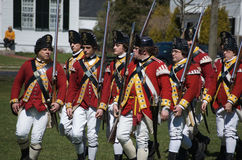Marching British Redcoats. A group of British redcoats marching with muskets at a reenactment of the Revolutionary war. It took place on the Battlegreen in Royalty Free Stock Photos