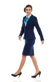 Marching Businesswoman In Blue Suit. Elegant woman in blue suit, skirt and high heels walking and looking at camera. Side view. Full length studio shot isolated royalty free stock image