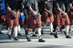 Marching parade. Caucasian legs of a Scottish musician parade group wearing traditional kilts playing bagpipes and marching together on the road outdoors stock photography