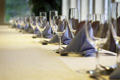 Marching wine glasses. A line of wine glasses fading off in the distance, shallow depth of field. yellow linen Stock Photography