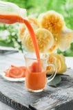 Marchwiany sok nalewa od dzbanka w szklaną filiżankę na tle róże Obrazy Stock