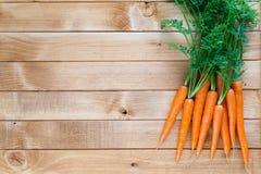 Marchwiany warzywo z liśćmi na drewnianym tle Obraz Stock