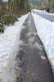 Marciapiede di inverno con sale sbrinante sopra Fotografia Stock