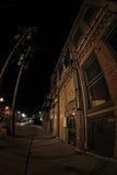 Marciapiede e costruzione scuri della città alla notte Fotografia Stock