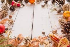 Marco abstracto de la Navidad con los conos, la corteza del pino, las bellotas, y los juguetes Fondo de madera blanco Imagen de archivo