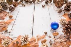 Marco abstracto de la Navidad con los conos, la corteza del pino, las bellotas, y los juguetes Fondo de madera blanco Fotografía de archivo