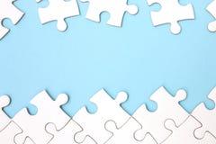 Marco blanco del rompecabezas en fondo azul en colores pastel Imagen de archivo libre de regalías