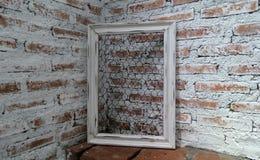 Marco blanco en la pared de la demostración del ladrillo bajo luz a través del tejado bajo luz del sol brillante Imagen de archivo libre de regalías