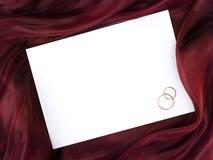 Marco blanco en seda y dos anillos de bodas Fotos de archivo