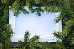 Marco blanco y ramas verdes de un árbol de navidad en el fondo de viejos, de madera tableros Visi?n superior con el espacio de la imágenes de archivo libres de regalías