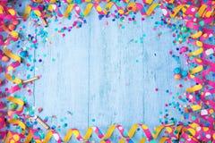 Marco colorido del cumpleaños o del carnaval con los artículos del partido en fondo de madera imagen de archivo libre de regalías