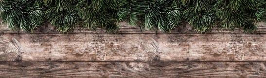 Marco creativo de la disposición hecho de las ramas del abeto de la Navidad, conos del pino en fondo de madera fotografía de archivo