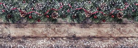 Marco creativo de la disposición hecho de ramas del abeto de la Navidad, de conos del pino y de cinta roja en fondo de madera imagen de archivo