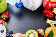 Marco de la aptitud con pesas de gimnasia, la toalla y las frutas frescas Imagen de archivo